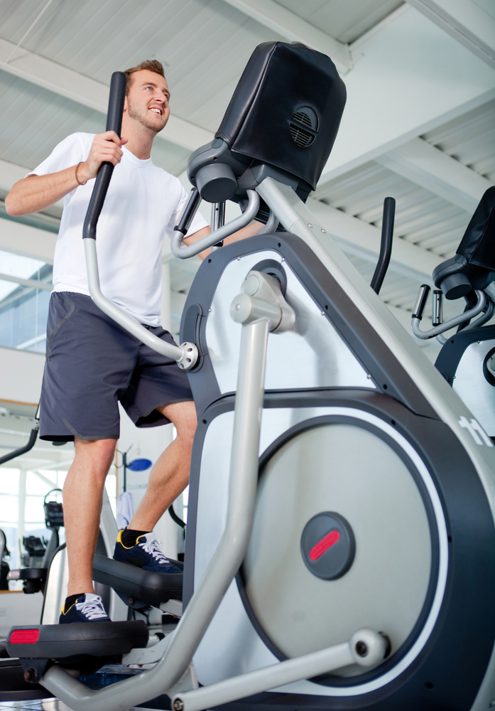 Man at the gym exercising on the xtrainer machine